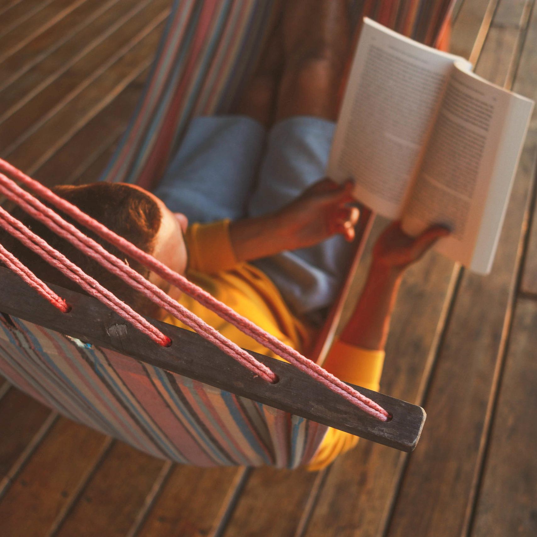 man reading a book in a hammock